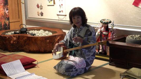 Reiseleiterin Miko spielt traditionelles Instrument